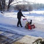 Bruder Georg schleudert den letzten Rest Schnee auf unserer Straße bei klirrender Kälte mit der Schneefräse am 12.12.2012 weg, nachdem es zwei Tage durchgeschneit hatte und auch die Schneefräse die letzten zwei Tage durchlief. Man sieht, dass der Schnee knietief neben der Straße ist.